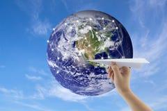 飞机在手中有在背景的地球的 免版税库存照片