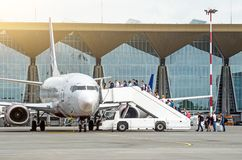 飞机在有乘客通道等待的搭乘的机场停放  免版税库存图片