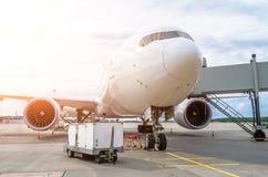 飞机在有乘客通道等待的搭乘的机场停放  库存照片