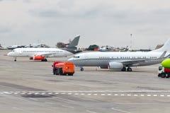 飞机在机场停放,接近填装的汽车 免版税库存图片