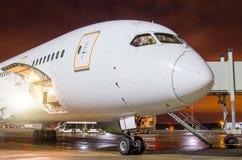 飞机在机场在晚上,看法鼻子驾驶舱停放了 免版税库存照片