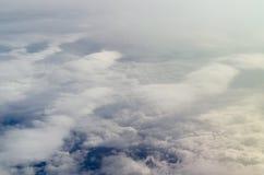飞机在蓬松云彩和天空蔚蓝的反光板视图 免版税库存照片