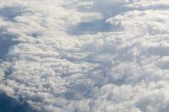 飞机在蓬松云彩和天空蔚蓝的反光板视图 免版税库存图片