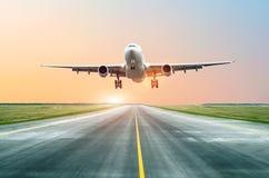 飞机在跑道登陆了在晚上在日落在机场 库存图片
