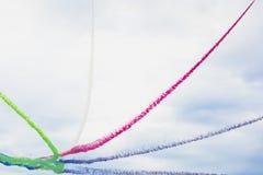 飞机明亮的多色烟足迹在特技展示、飞行的显示和特技飞行的 免版税库存图片