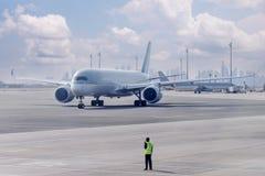 飞机是由地勤人员引导的到停车场 免版税库存照片
