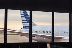 飞机机体尾巴看法通过窗口在机场 免版税库存图片