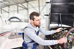 飞机机械员修理在机场hanga的一台飞机发动机 库存照片
