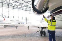 飞机机械员地勤人员检查并且检查涡轮 免版税库存照片