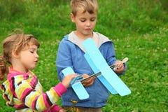 飞机男孩女孩递玩具 免版税库存照片