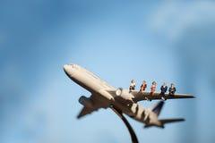 飞机的微型人使用当背景旅行 免版税库存图片