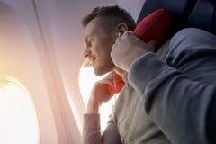 飞机的男性乘客听到音乐并且享用睡觉的枕头在椅子 免版税库存照片