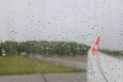 飞机的翼的看法通过窗口湿从雨(被弄脏的墙纸) 图库摄影