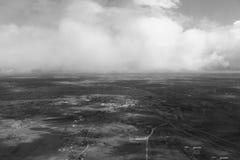 从飞机看见的云彩,阳光,土壤背景黑色白色 免版税库存照片