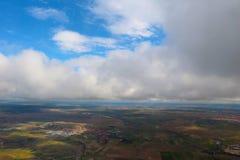 从飞机看见的云彩,阳光,土壤背景 库存图片