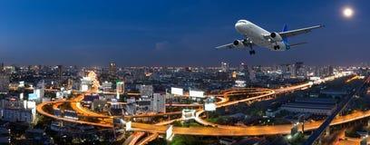 飞机离开在全景城市在暮色场面 免版税库存图片