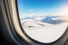 飞机窗口和顶视图在天空是云彩和太阳 旅行大气  免版税图库摄影