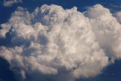 从飞机窗口的鸟瞰图到一朵蓬松云彩 免版税库存图片
