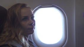 飞机窗口背景的画象年轻女人 看对飞机在天空的窗口飞行的卷曲女孩 妇女乘客 股票录像