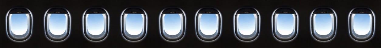 飞机窗口10和反对蓝色的意想不到的软的白色云彩 免版税库存图片
