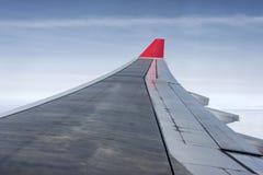 飞机翼从空气的在天空小翅膀红色上色了航空公司蓝天云彩 图库摄影