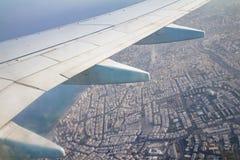 飞机翼在天空和在有特拉维夫大厦的土地  免版税库存照片