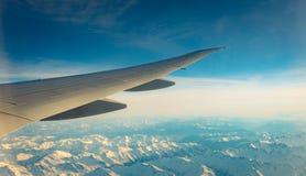 飞机翼在山盖子的有白雪的 r r ?? 图库摄影