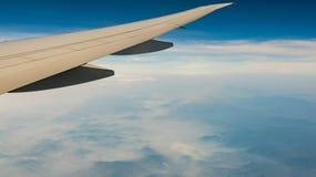 飞机翼在山盖子的有雾和薄雾在天空蔚蓝的飞机飞行的 r 商业空气 免版税图库摄影