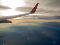 飞机翼从窗口的与美好的阳光和云彩 库存照片