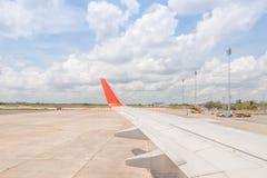 飞机翼从窗口的在着陆的机场 免版税库存图片