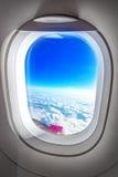 飞机舷窗窗口和夏天云彩 免版税库存图片