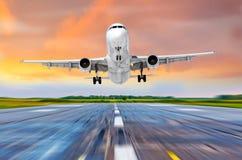 飞机飞行在一个跑道机场的到来着陆在一明亮的红色日落cloudscape期间的晚上 图库摄影