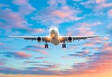 飞机飞行在一个跑道机场的到来着陆在一明亮的红色日落cloudscape期间的晚上 免版税库存图片