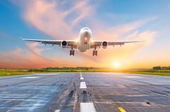 飞机飞行在一条跑道的到来着陆在明亮的红色日落阳光期间的晚上 免版税库存图片