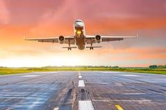 飞机飞行在一条跑道的deperture着陆在明亮的红色日落期间的晚上 免版税库存照片