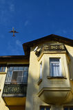 飞机飞行在房子 免版税库存照片