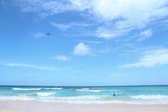 飞机飞行在热带海滩 免版税库存照片