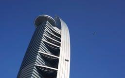 飞机飞行在现代大厦 库存图片