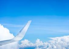 飞机飞行翼在云彩和蓝天上的 免版税库存照片