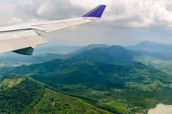 飞机飞行翼在多云天空的在绿色山 图库摄影