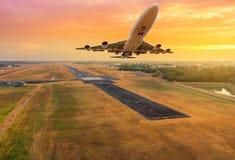 飞机飞行从日落的跑道离开 免版税图库摄影