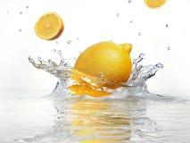 飞溅入清楚的水的柠檬。 免版税库存图片