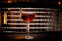 飞溅入玻璃的红色马蒂尼鸡尾酒鸡尾酒在黑暗的背景 免版税库存照片