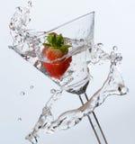 飞溅入马蒂尼鸡尾酒玻璃的草莓 免版税库存图片