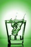 飞溅入玻璃,冰块的冰块滴下了入杯水,新鲜,冷水,隔绝在绿色背景 免版税库存图片