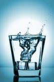 飞溅入玻璃,冰块的冰块滴下了入杯水 免版税库存图片