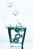 飞溅入玻璃,冰块的冰块滴下了入杯水 库存图片