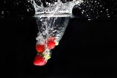 飞溅入水的三strawberrys 免版税库存图片