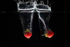 飞溅入水的两strawberrys 免版税库存图片