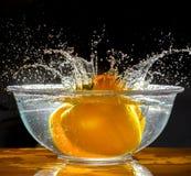 飞溅入水的黄色胡椒菜 免版税图库摄影